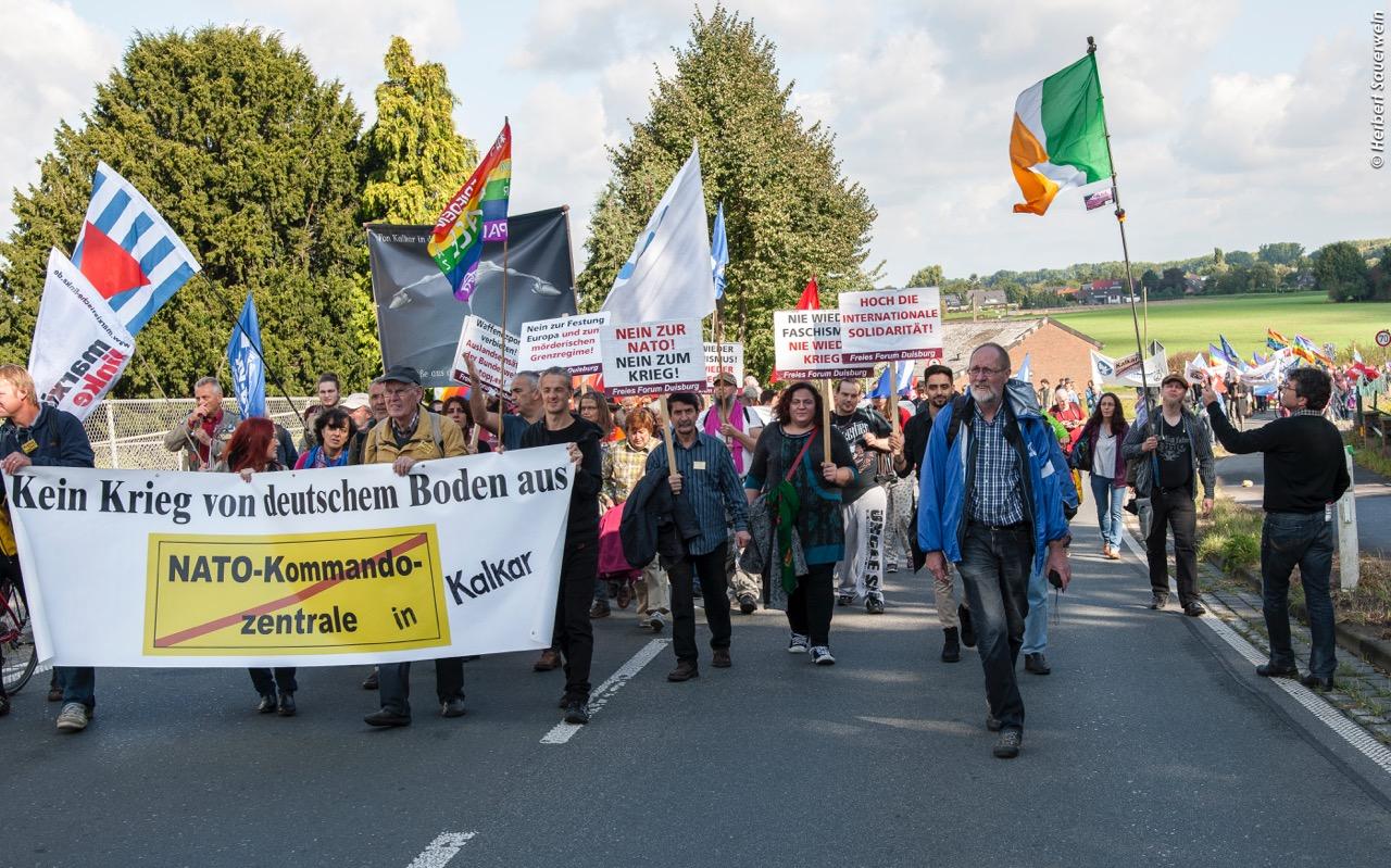 Ein Demozug mit Friedensfahnen und Transparenten.