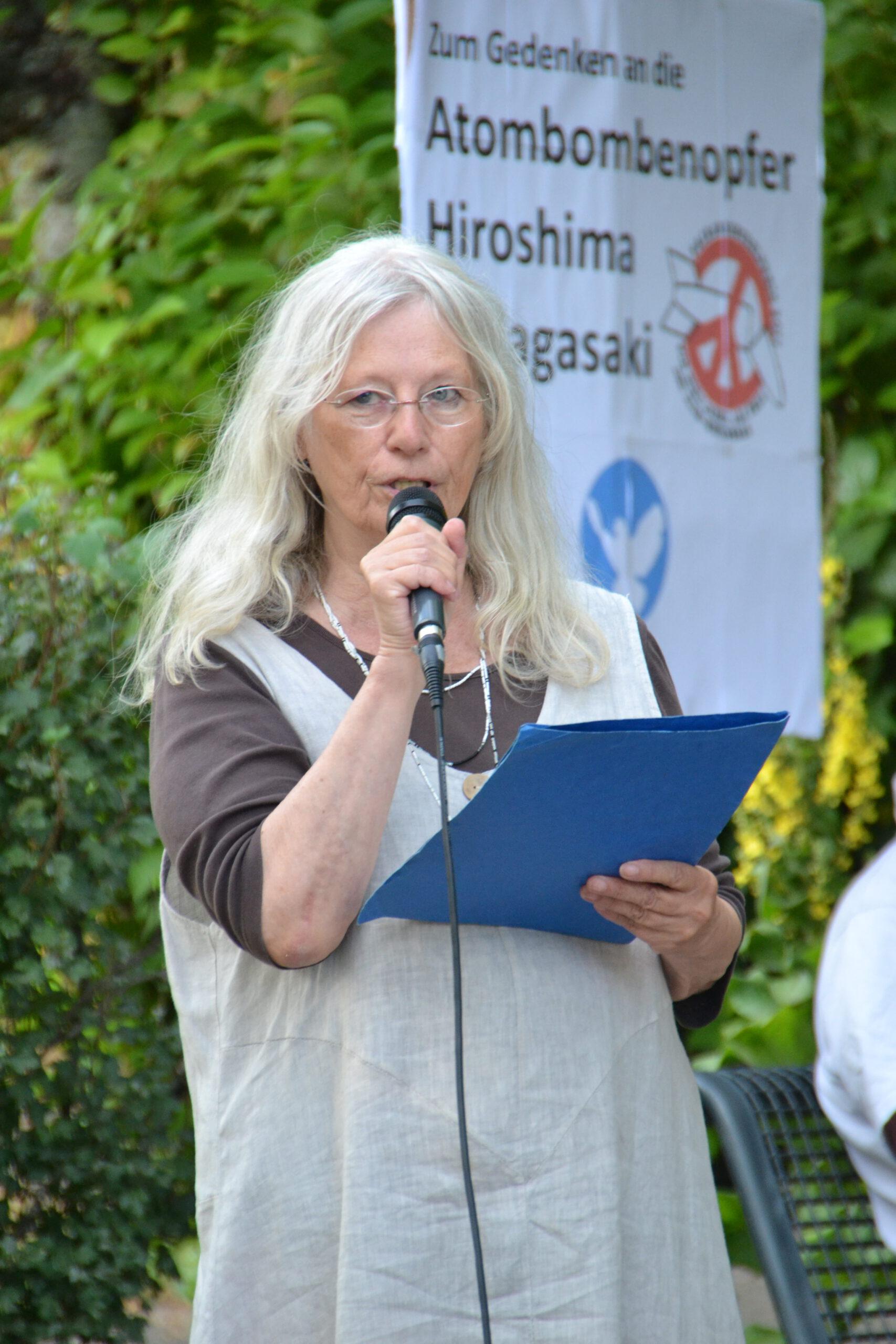"""Eine freundliche ältere Dame mit langen weich gewellten weißen Haaren und leinenfarbenem Sommerkleid spricht in ein Mikro. Im Hintergrund sind eine Friedenstaube, das ICAN-Symbol und """"Hiroshima"""" und """"Nagasaki"""" auf einem Transparent zu erkennen."""